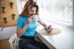 Όμορφος ξανθός καφές κατανάλωσης γυναικών και ανάγνωση των ειδήσεων Στοκ εικόνες με δικαίωμα ελεύθερης χρήσης