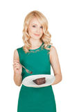 Όμορφος ξανθός κρατά ένα πιάτο με ένα κομμάτι μιας πίτας σοκολάτας Στοκ εικόνα με δικαίωμα ελεύθερης χρήσης