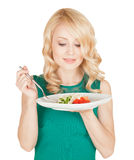 Όμορφος ξανθός κρατά ένα πιάτο με τη σαλάτα από τα λαχανικά Στοκ Φωτογραφίες