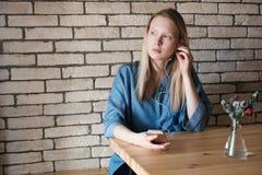 Όμορφος ξανθός με ένα τηλέφωνο στο χέρι της, άγγιξε το ακουστικό στο αυτί που φορά στο μπλε πουκάμισο στον πίνακα καφέδων Στοκ Φωτογραφίες
