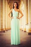 Όμορφος ξανθός με μια μακριά σγουρή τρίχα σε ένα μακρύ φόρεμα βραδιού σε στατικό υπαίθρια κοντά στο αναδρομικό εκλεκτής ποιότητας Στοκ φωτογραφίες με δικαίωμα ελεύθερης χρήσης