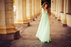 Όμορφος ξανθός με μια μακριά σγουρή τρίχα σε ένα μακρύ φόρεμα βραδιού σε στατικό υπαίθρια κοντά στο αναδρομικό εκλεκτής ποιότητας Στοκ Φωτογραφίες