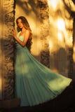 Όμορφος ξανθός με μια μακριά σγουρή τρίχα σε ένα μακρύ φόρεμα βραδιού σε στατικό υπαίθρια κοντά στο αναδρομικό εκλεκτής ποιότητας Στοκ φωτογραφία με δικαίωμα ελεύθερης χρήσης
