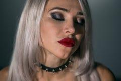 Όμορφος ξανθός με τα κόκκινα χείλια σε ένα σκοτεινό υπόβαθρο σε ένα περιλαίμιο στοκ φωτογραφία με δικαίωμα ελεύθερης χρήσης