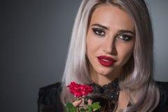 Όμορφος ξανθός με τα κόκκινα χείλια σε ένα σκοτεινό υπόβαθρο σε ένα περιλαίμιο στοκ φωτογραφίες