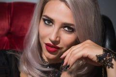 Όμορφος ξανθός με τα κόκκινα χείλια σε ένα σκοτεινό υπόβαθρο σε ένα περιλαίμιο στοκ φωτογραφίες με δικαίωμα ελεύθερης χρήσης