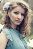 Όμορφος ξανθός με το όμορφο hairstyle στο εκλεκτής ποιότητας μπλε φόρεμα σε ένα πολύβλαστο magnolia κήπων άνοιξη Στοκ Εικόνες