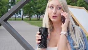 Όμορφος ξανθός μιλά στο τηλέφωνο κατά τη διάρκεια ενός μεσημεριανού γεύματος σε έναν καφέ r Νέα γυναίκα με ένα smartphone σε την απόθεμα βίντεο