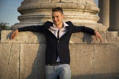 Όμορφος ξανθός νεαρός άνδρας με τη μαρμάρινη στήλη πίσω από τον Στοκ φωτογραφία με δικαίωμα ελεύθερης χρήσης