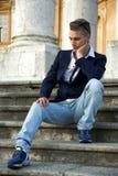 Όμορφος ξανθός νεαρός άνδρας με τις μαρμάρινες στήλες πίσω από τον Στοκ εικόνες με δικαίωμα ελεύθερης χρήσης