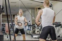 Όμορφος ξανθός νεαρός άνδρας που ασκεί το Pecs στον εξοπλισμό γυμναστικής Στοκ Εικόνα