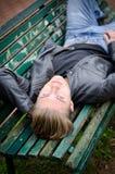 Όμορφος ξανθός νεαρός άνδρας που βάζει στον πάγκο πάρκων Στοκ Εικόνα