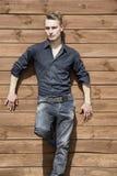 Όμορφος ξανθός νεαρός άνδρας που στέκεται έξω ενάντια στον ξύλινο τοίχο Στοκ Φωτογραφίες