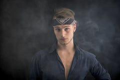 Όμορφος ξανθός νεαρός άνδρας που φορά το bandana, καπνός γύρω από τον Στοκ Εικόνες