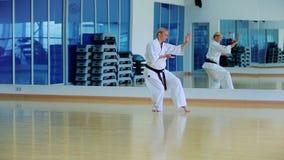 Όμορφος ξανθός παρουσιάζει karate τέχνασμα στη γυμναστική φιλμ μικρού μήκους