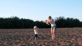 Όμορφος ξανθός σε ένα καπέλο mom και την κόρη προωθεί έναν ικτίνο στην παραλία απόθεμα βίντεο