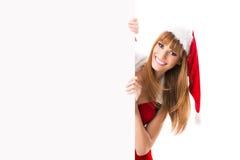 Όμορφος ξανθός σε ένα καπέλο santa που κοιτάζει από πίσω από έναν κενό πίνακα διαφημίσεων Στοκ φωτογραφία με δικαίωμα ελεύθερης χρήσης