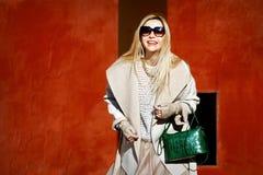 Όμορφος ξανθός σε ένα μπεζ παλτό και με μια τσάντα των πράσινων χρωμάτων που χαμογελούν υπαίθρια Στοκ φωτογραφία με δικαίωμα ελεύθερης χρήσης
