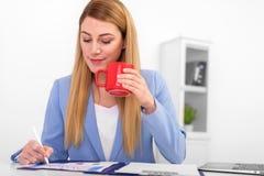 Όμορφος ξανθός σε ένα μπλε κοστούμι με ένα κόκκινο φλυτζάνι στο χέρι της στην εργασία Στοκ Φωτογραφία