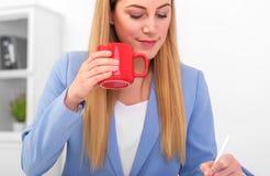Όμορφος ξανθός σε ένα μπλε κοστούμι με ένα κόκκινο φλυτζάνι στο χέρι της στην εργασία Στοκ Φωτογραφίες