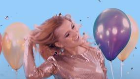Όμορφος ξανθός σε ένα χρυσό φόρεμα προωθεί confit Χαμογελά και χορεύει Απολαμβάνει τις διακοπές Δίπλα στα μπαλόνια της φιλμ μικρού μήκους