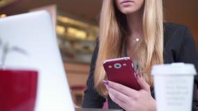 Όμορφος ξανθός στο μαύρο σακάκι κάθεται στον καφέ Εργάζεται με το smartphone και το σημειωματάριό της φιλμ μικρού μήκους