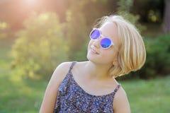 Όμορφος ξανθός το κορίτσι στην ελαφριά γιόγκα άσκησης ιματισμού σε ένα χαλί στο πάρκο Υγιής τρόπος ζωής Στοκ Φωτογραφία