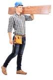 Όμορφος ξυλουργός που φέρνει μερικές σανίδες Στοκ φωτογραφία με δικαίωμα ελεύθερης χρήσης