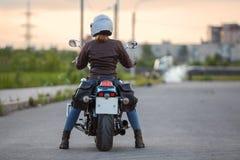Όμορφος οδηγός μοτοσικλετών γυναικών που περιμένει στο δρόμο στο βράδυ, οπισθοσκόπο Στοκ φωτογραφία με δικαίωμα ελεύθερης χρήσης