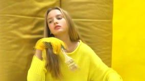 Όμορφος οικοδόμος κοριτσιών που κρατά μια βούρτσα χρωμάτων και που θέτει στη κάμερα στο κίτρινο backgrond απόθεμα βίντεο