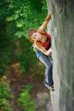 Όμορφος ορειβάτης γυναικών που αναρριχείται στον απότομο βράχο με το σχοινί Στοκ Εικόνες
