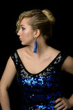 Όμορφος ο ξανθός με τη σγουρή τρίχα σε ένα μπλε φόρεμα με το τσέκι Στοκ Εικόνες