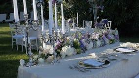 Όμορφος πίνακας που θέτουν με τα πιατικά και τα λουλούδια για ένα κόμμα, δεξίωση γάμου ή άλλο εορταστικό γεγονός Στις ακτές απόθεμα βίντεο