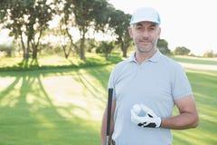Όμορφος παίκτης γκολφ που στέκεται με τη σφαίρα γκολφ Στοκ Εικόνες
