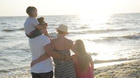 Όμορφος πατέρας και ελκυστική μητέρα με δύο κόρες που ξοδεύουν το χρόνο μαζί κοντά στη θάλασσα κατά τη διάρκεια του ηλιοβασιλέματ απόθεμα βίντεο