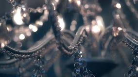 Όμορφος πολυέλαιος, με τα διαφανή κρεμαστά κοσμήματα και τους καίγοντας λαμπτήρες, κινηματογράφηση σε πρώτο πλάνο φιλμ μικρού μήκους