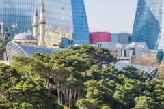 Όμορφος, πολυόροφο κτίριο, κομψά κτήρια που στέκεται σε ένα υψηλό βουνό Αντανάκλαση της πόλης και της θάλασσας στα παράθυρα γυαλι Στοκ εικόνα με δικαίωμα ελεύθερης χρήσης
