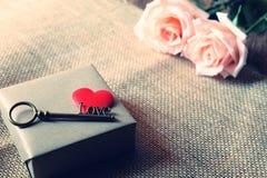 Όμορφος πορτοκαλής-ρόδινος αυξήθηκε με το κλειδί μορφής αγάπης στην κόκκινη καρδιά σατέν δύο Μαλακός τόνος για ρομαντικό Valentin στοκ φωτογραφία με δικαίωμα ελεύθερης χρήσης