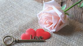 Όμορφος πορτοκαλής-ρόδινος αυξήθηκε με το κλειδί μορφής αγάπης στην κόκκινη καρδιά σατέν δύο Μαλακός τόνος για ρομαντικό Valentin στοκ φωτογραφίες με δικαίωμα ελεύθερης χρήσης