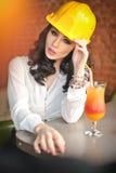 Όμορφος πολιτικός μηχανικός γυναικών με το κίτρινο κράνος που παίρνει ένα σπάσιμο μπροστά από το χυμό από πορτοκάλι Νέος θηλυκός  Στοκ Φωτογραφία
