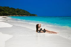 Όμορφος προκλητικός πρότυπος ήλιος κοριτσιών μπικινιών που μαυρίζουν στην τροπική παραλία Ο Στοκ Εικόνες