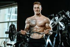 Όμορφος πρότυπος νεαρός άνδρας που επιλύει στη γυμναστική Στοκ Φωτογραφία