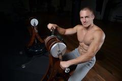 Όμορφος πρότυπος νεαρός άνδρας που επιλύει στη γυμναστική Στοκ Φωτογραφίες