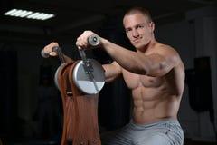 Όμορφος πρότυπος νεαρός άνδρας που επιλύει στη γυμναστική Στοκ Εικόνες