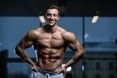Όμορφος πρότυπος νεαρός άνδρας workout στη γυμναστική Στοκ Φωτογραφία