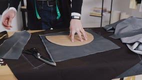 Όμορφος ράφτης που εργάζεται στο στούντιό του, που επισύρει την προσοχή το πρότυπο στο ύφασμα Δημιουργικός μια εργασία του ράφτη  απόθεμα βίντεο