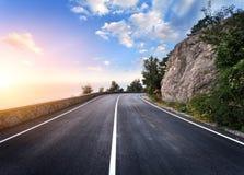 Όμορφος δρόμος ασφάλτου βουνών με τους βράχους, μπλε ουρανός στο ηλιοβασίλεμα στοκ φωτογραφία με δικαίωμα ελεύθερης χρήσης