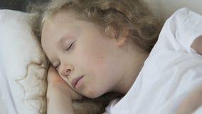Όμορφος σγουρός ύπνος παιδιών τρίχας ξανθός στο κρεβάτι της, υγιής ύπνος, κινηματογράφηση σε πρώτο πλάνο φιλμ μικρού μήκους