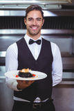Όμορφος σερβιτόρος που κρατά ένα πιάτο των μακαρονιών μελανιού καλαμαριών Στοκ Φωτογραφίες