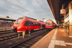 Όμορφος σιδηροδρομικός σταθμός με τη σύγχρονη κόκκινη αμαξοστοιχία περιφερειακού σιδηροδρόμου στο ηλιοβασίλεμα Στοκ φωτογραφία με δικαίωμα ελεύθερης χρήσης